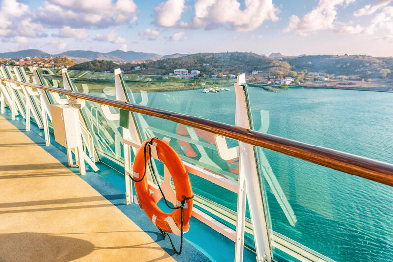 Cruise ship deck with life ring and view over the Caribbean Sea with island in the background