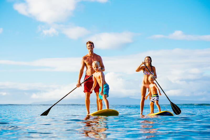 Father, mother and two sons on paddle boards outside the marina on an around the world cruise ship