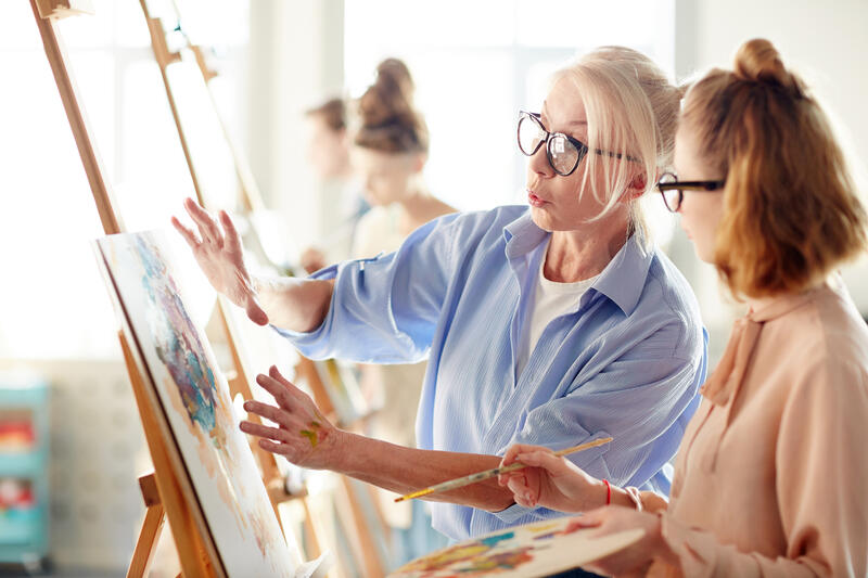 Woman wearing blue shirt and glasses - an art teacher directing an art student working at an easel in the art studio on an around the world cruise ship