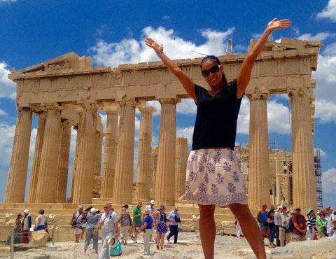 Woman standing in front of the Acropolis in Athens Greece with her hands raised while cruising around the world