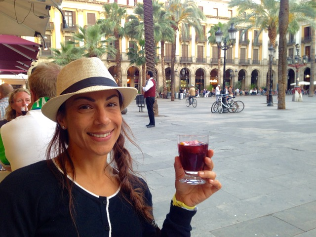 Woman sitting in a piazza in Barcelona wearing a hat and holding a glass of sangria while living on a cruise ship