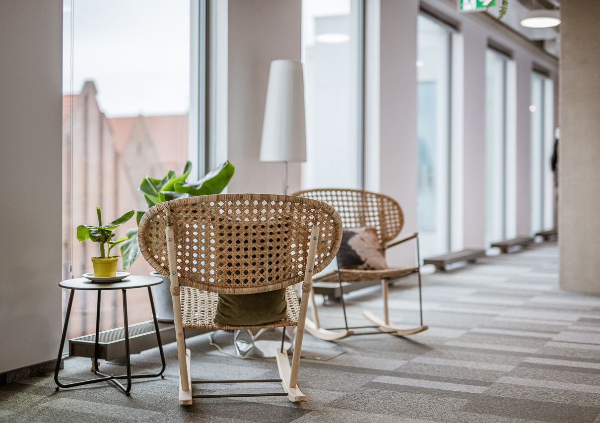 Condo ship office with two rattan rocking chairs facing a window view of historic brick architecture