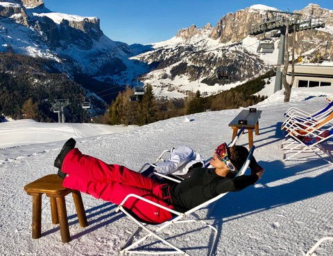 Woman wearing ski clothes lounging on a sun chair in the Dolomites.