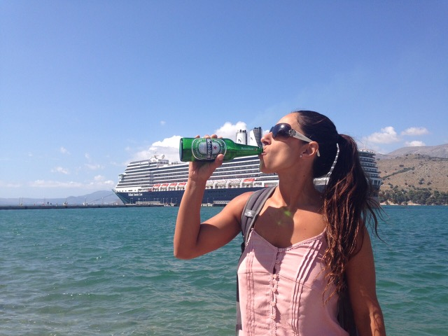 Woman drinking from a bottle with cruise ship in the background and traveling through Greece