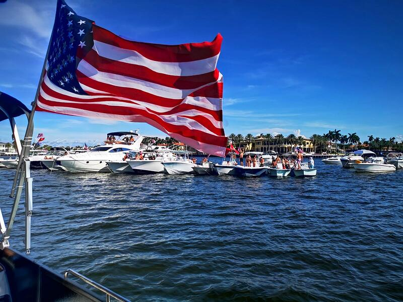 American flag flying from the side of a boat in a marina celebrating Independence Day