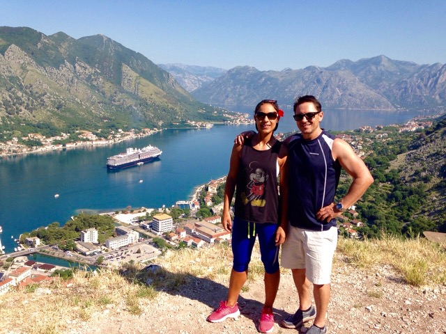 Couple standing on the top of a hill in Kotor Montenegro with city, hills and cruise ship in the background