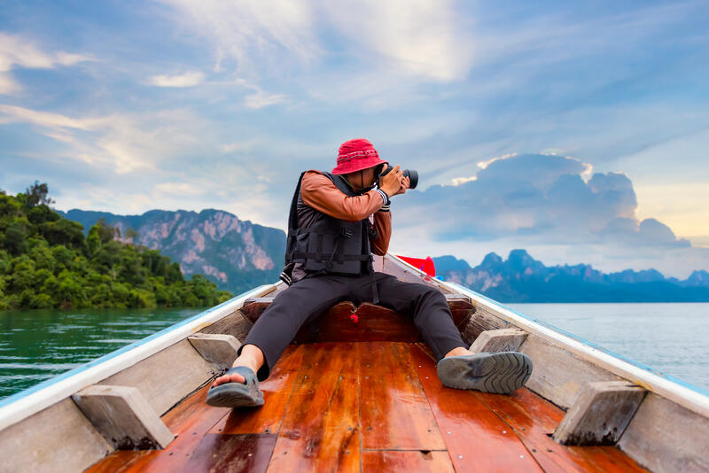 Person with a travel lifestyle sitting on the bow of a wooden boat taking a photograph of the mountains in the background