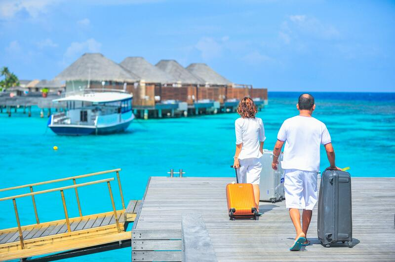 Man and woman carrying luggage on dock in the Maldives