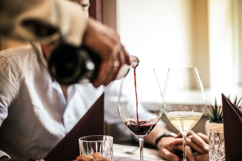 Sommelier pouring a glass of good red wine