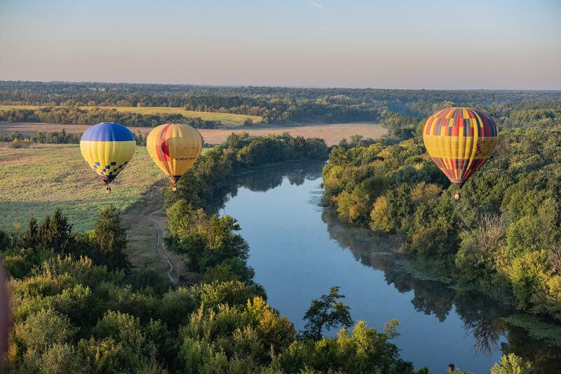 Three hot air balloons fly over wine region and river
