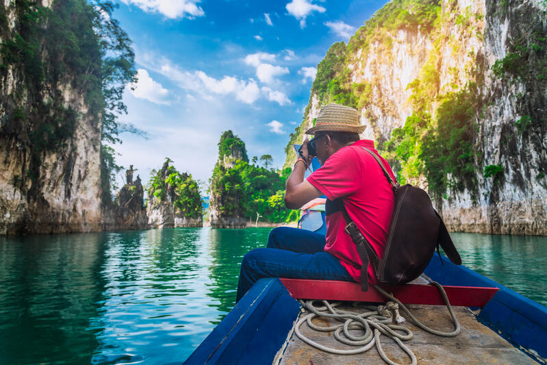 Man sitting on bow of boat taking photograph on around the world cruise in Thailand