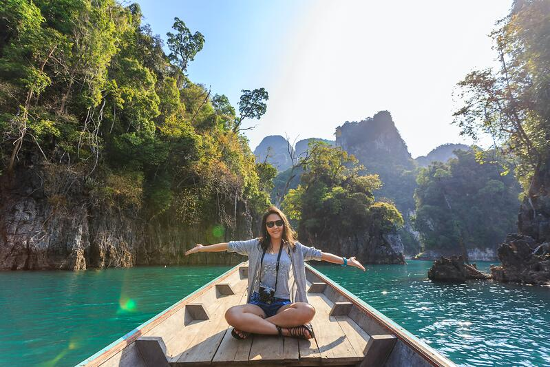 Woman smiling while traveling on a longboat in Asia with mountains in the background