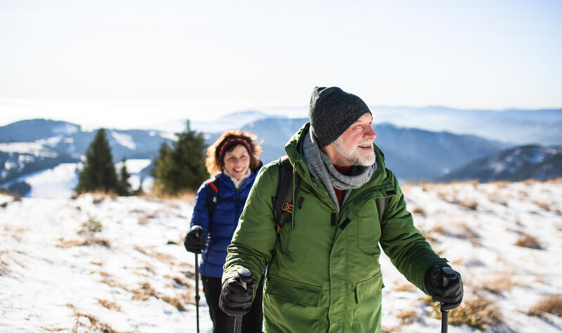 Man and woman snowshoeing in the mountains