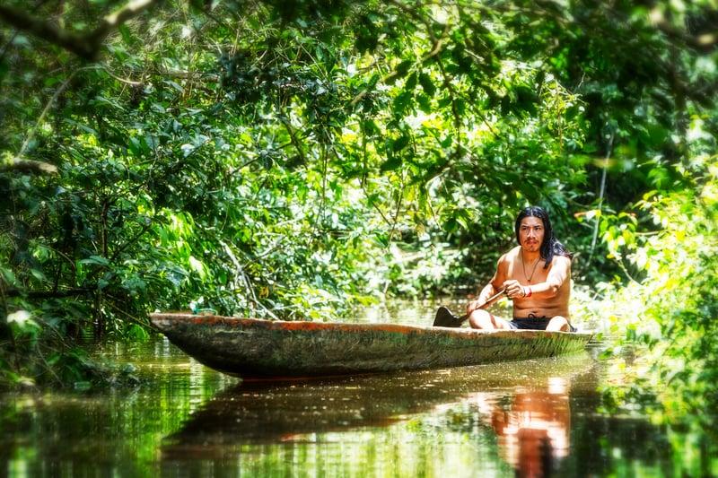 Man paddling dugout canoe on around the world adventure